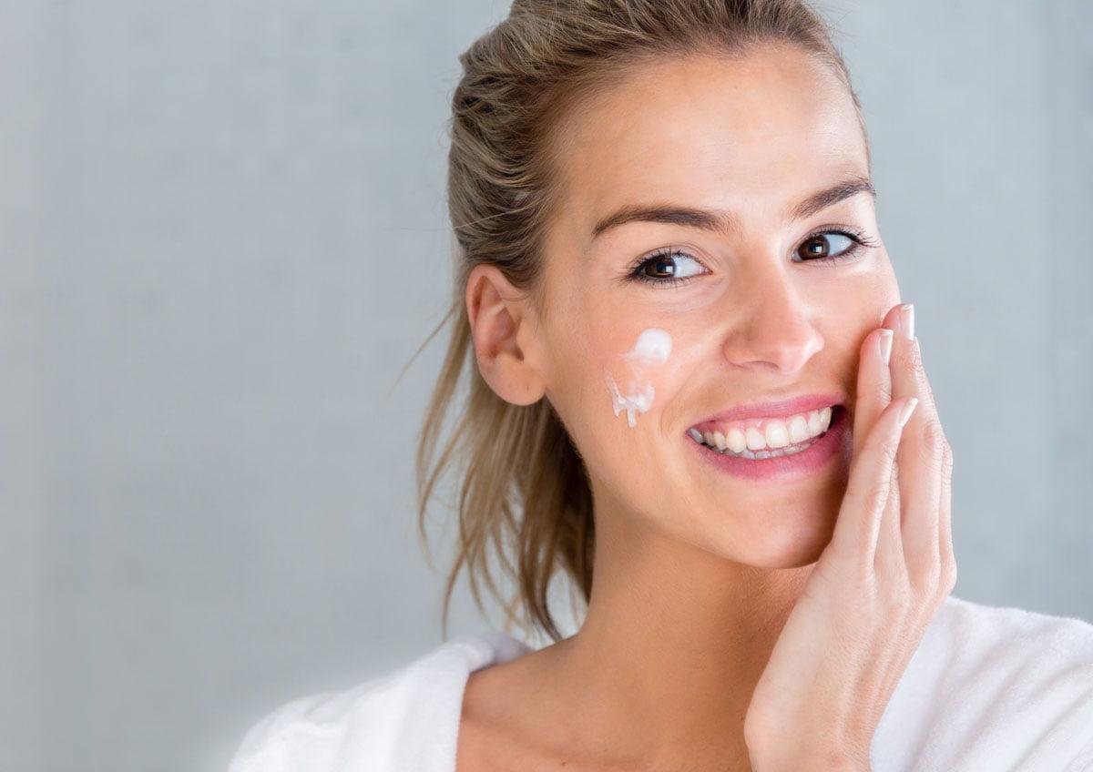 smiling woman applying cream to cheeks