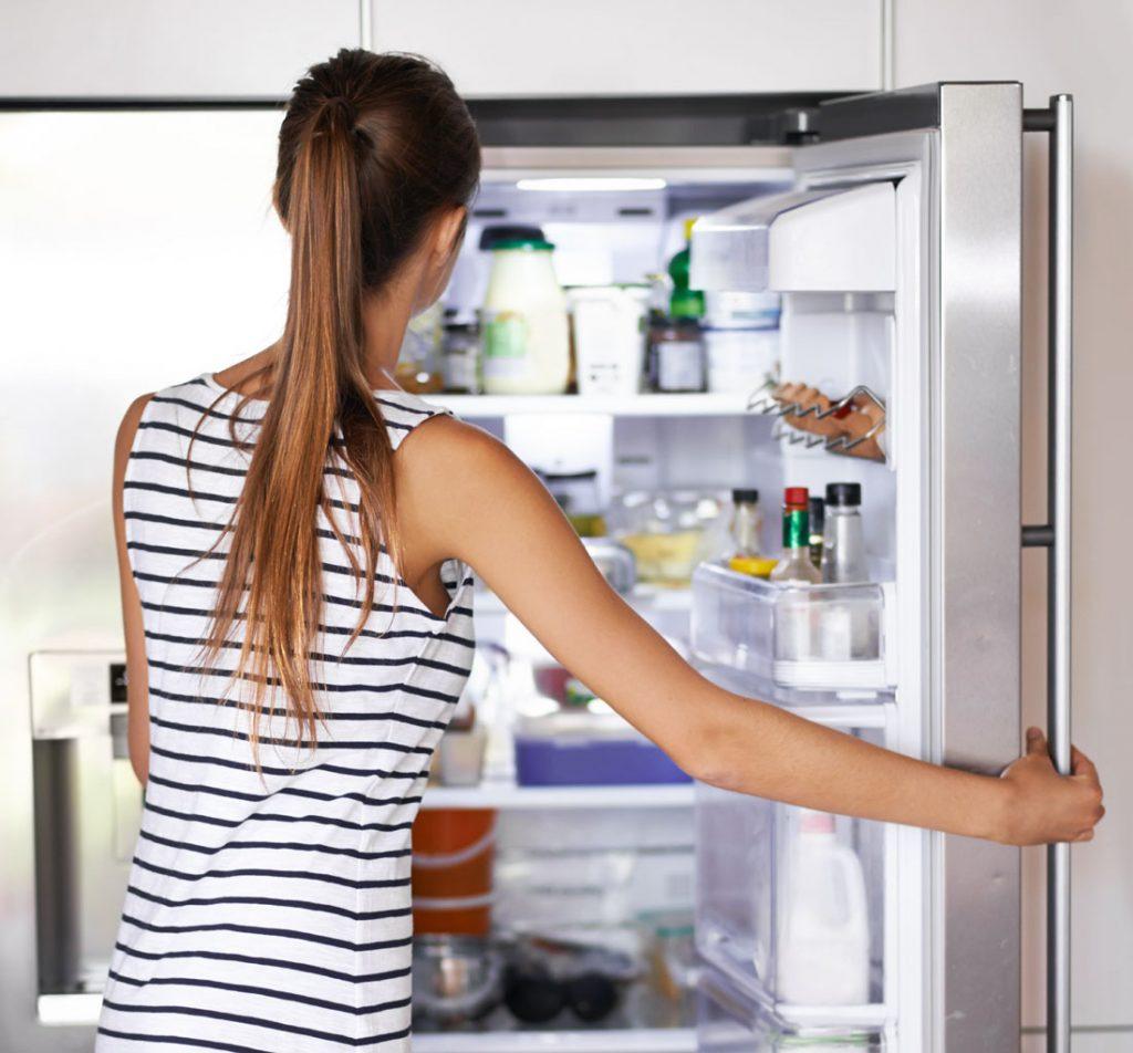 woman standing in front of open refrigerator door